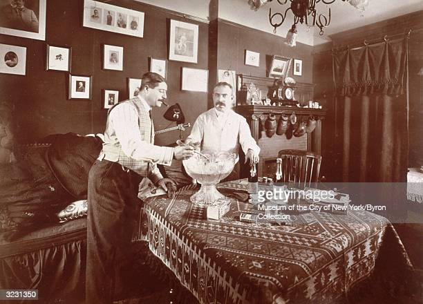 One man serves another from a crystal punch bowl while standing at a table with packets of cigarettes cigars and a champagne bottle in the Edwardian...