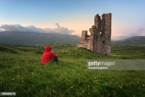 one man sitting near ardvreck castle, loch assynt, scotland. - oude ruïne stockfoto's en -beelden