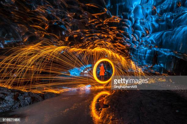 one man spinning the fire in ice cave, iceland - cave fire stock photos and pictures