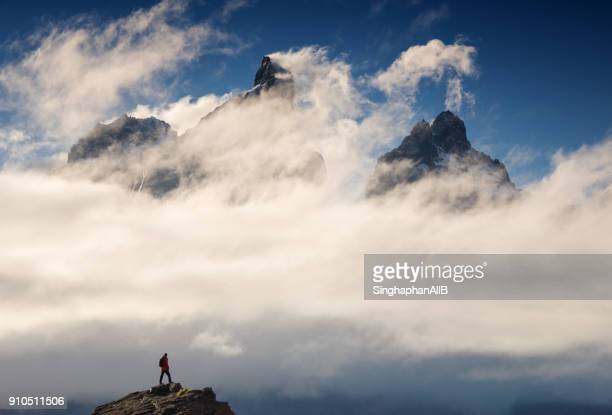 one man standing among the cloud looking at view of majestic scale of torres del paine, chile - patagonia foto e immagini stock