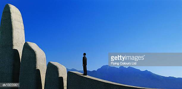 One Man Standing Looking at Rock Formation