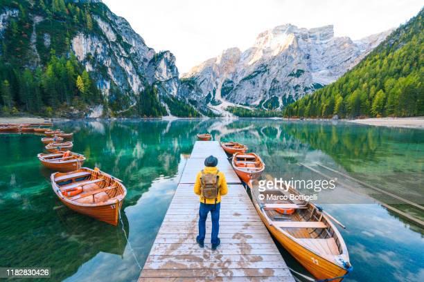 one man standing on a pier at lake braies, south tyrol, italy - vertäut stock-fotos und bilder