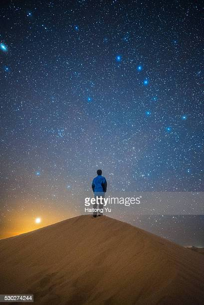 one man standing on sand dune glaring at big dippers - grande carro costellazione foto e immagini stock