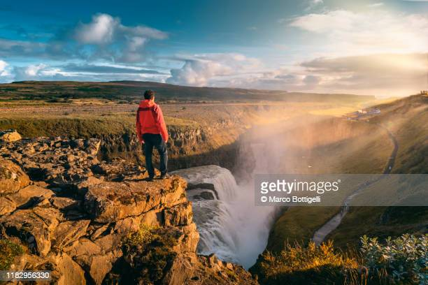 one man standing on top of gullfoss waterfall, iceland - 雄大 ストックフォトと画像