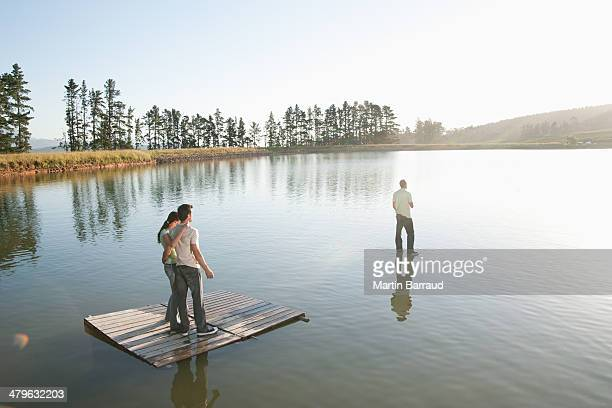 One man standing on water with man and woman watching