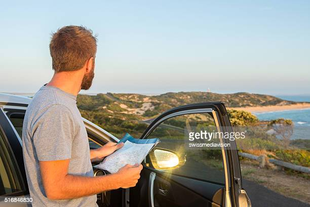 One man stands beside car and reads map