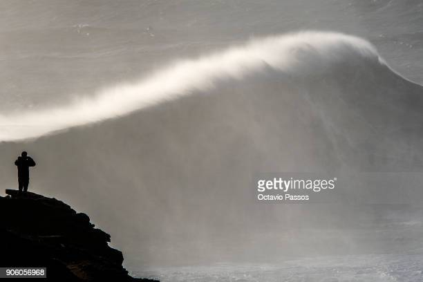 One man take photos of the waves and surfers during a surf session at Praia do Norte on January 17 2018 in Nazare Portugal
