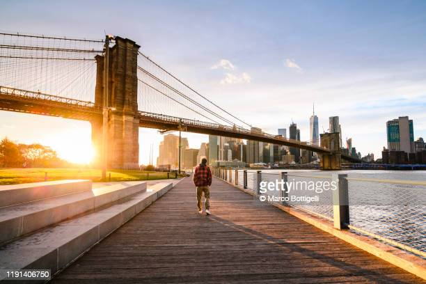 one man walking on the old dock under brooklyn bridge at sunset, new york city - usa stock pictures, royalty-free photos & images