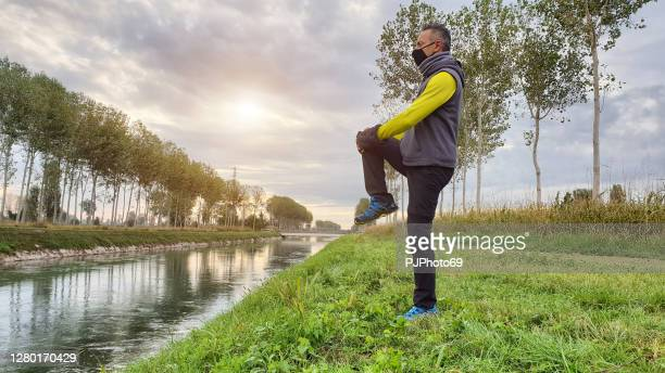 one man with mask doing some outdoor workout during covid period near a river - pjphoto69 stock pictures, royalty-free photos & images