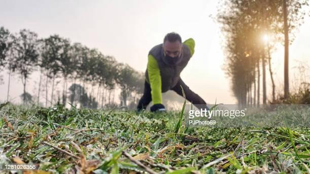 un uomo (concentrati sull'erba) con la maschera che fa un po 'di allenamento all'aperto durante il periodo covid vicino a un fiume al mattino presto - pjphoto69 foto e immagini stock