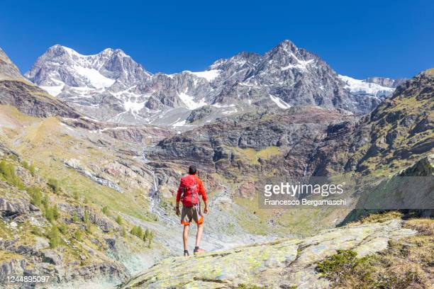 one man with red clothes and backpack looks the mountain landscape. - italia stock-fotos und bilder