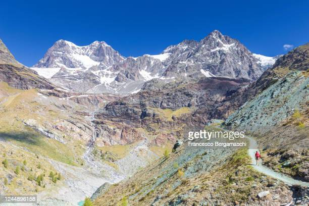 one man with red clothes and backpack walk on a path with view on the mountains. - italia stock-fotos und bilder