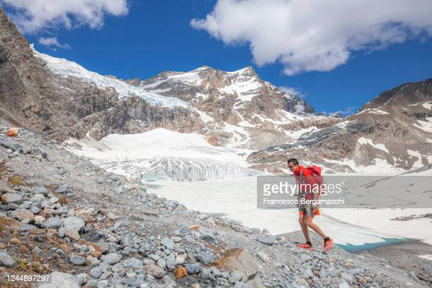 one man with red clothes and backpack walks uphill path with view on the glacier. - italia stock-fotos und bilder