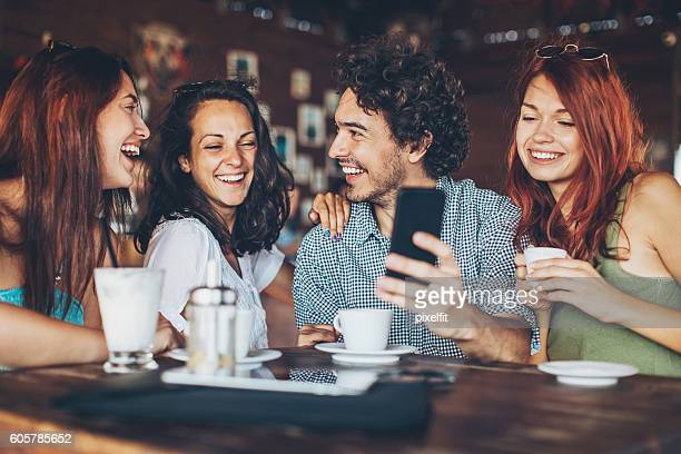 one man with three women in cafe - man met een groep vrouwen stockfoto's en -beelden