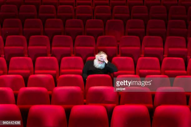 One man with white beard sits in Empty cinema, asleep