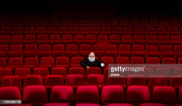 one man with white beard sits in empty cinema or theatre - one man only stock pictures, royalty-free photos & images