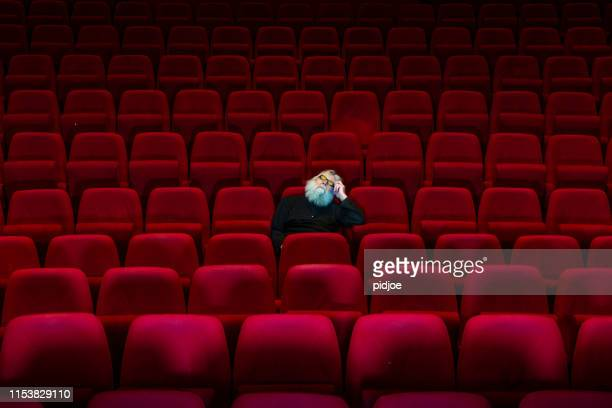 one man with white beard sits in empty cinema or theatre with comfortable red seats, sleeping - theatrical performance stock pictures, royalty-free photos & images