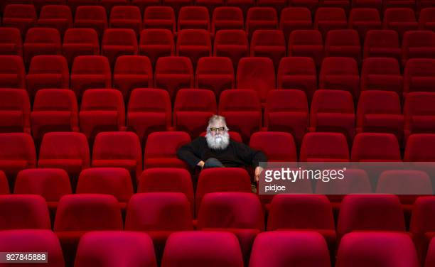 one man with white beard sits in empty cinema or theatre with comfortable red seats - opera stock pictures, royalty-free photos & images