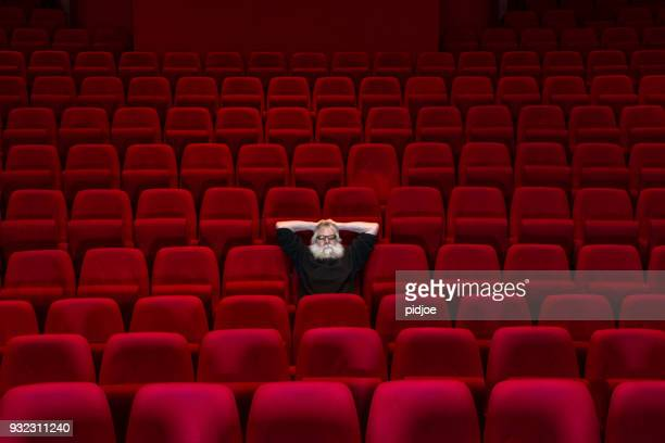 One man with white beard sits in Empty cinema or theatre with comfortable red seats