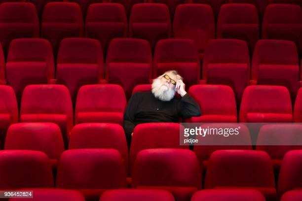 One man with white beard sits in Empty cinema or theatre with comfortable red seats, sleeping