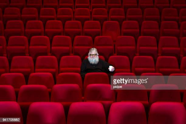 One man with white beard sits in Empty cinema