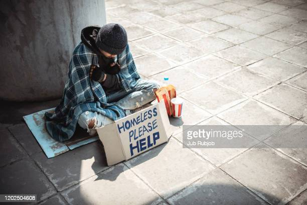 one man, young homeless sitting on the street and begging. - sin techo fotografías e imágenes de stock