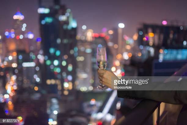 One man's hand is holding a glass wine with the bokeh of city lights in the background