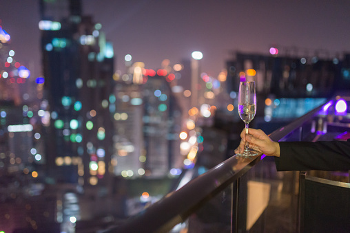 One man's hand is holding a glass wine with the bokeh of city lights in the background - gettyimageskorea