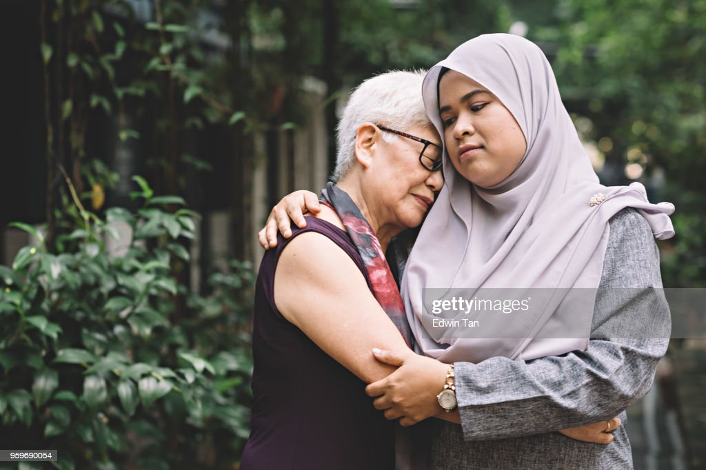 one matured asian chinese female talking and hugging a middle age asian malay female with sad expression : Stock Photo