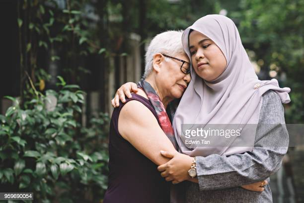 one matured asian chinese female talking and hugging a middle age asian malay female with sad expression - grief stock pictures, royalty-free photos & images