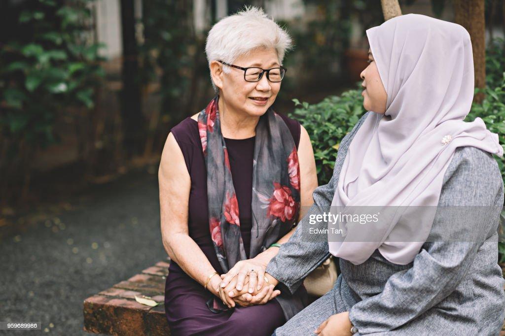 eine gereifte asiatische chinesische Frau im Gespräch mit asiatischen malaiischen Frau mittleren Alters : Stock-Foto
