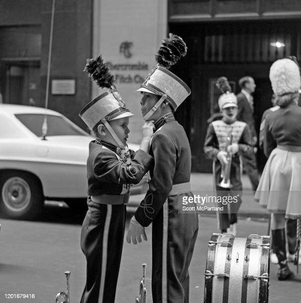 One member of an elementary school marching band helps another adjust his uniform, prior to the St Patrick's Day Parade, New York, New York, March...