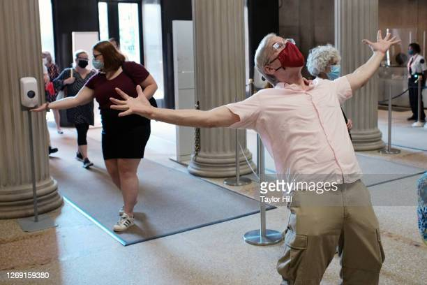 One member sanitizes their hands as another member celebrates at The Metropolitan Museum of Art during its first day open to members since March on...