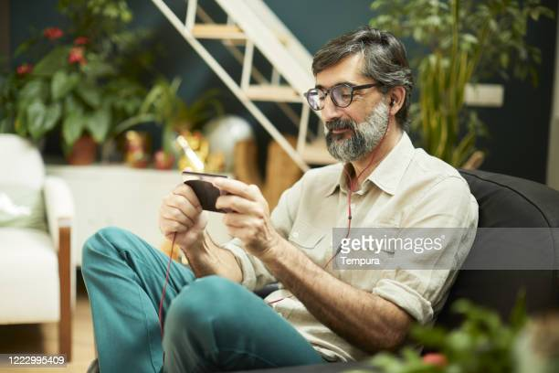 one mid adult man on a video call streaming tv - live broadcast stock pictures, royalty-free photos & images