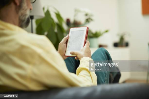 one mid adult man reading on an e-reader seen from behind. - e reader stock pictures, royalty-free photos & images