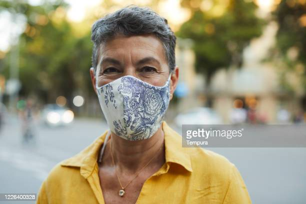 one midle aged woman wearing a protective mask and smiling - pollution mask stock pictures, royalty-free photos & images