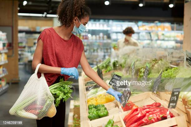 one millenial costumer choosing vegetables in a grocery store. - comida e bebida imagens e fotografias de stock