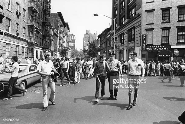 One month after the demonstrations and conflict at the Stonewall Inn activist Marty Robinson a police officer and others walk in the street with...