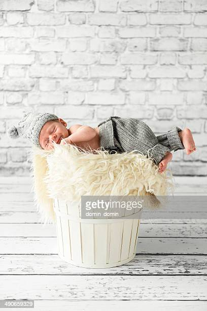 One month old baby boy lying on white basket, interior