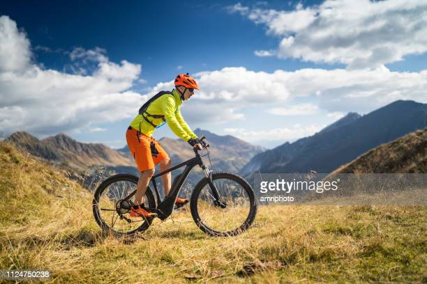 one mountain biker high up in european alps - mountain bike stock pictures, royalty-free photos & images