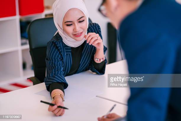 one muslim businesswomen having discussion in a meeting room - rifka hayati stock pictures, royalty-free photos & images