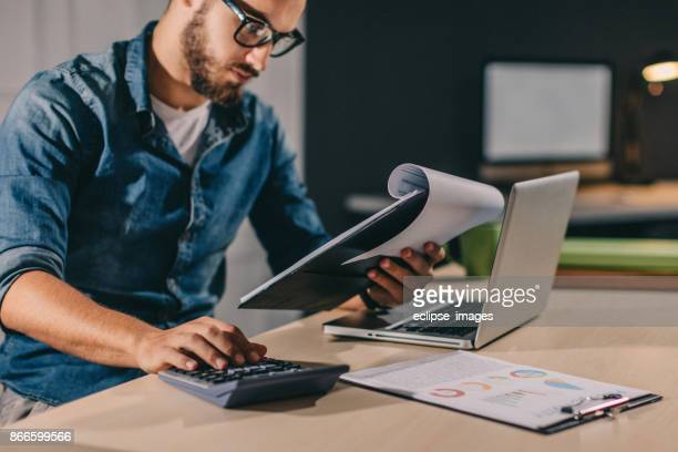 one night at office - calculator stock photos and pictures