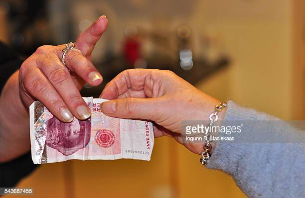 One norwegian paying 100 norwegian krones to another norwegian woman