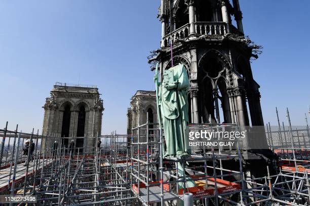 TOPSHOT One of 16 copper statues sitting 50 meters above the ground is lifted off the NotreDamedeParis Cathedral to be taken for restoration on April...