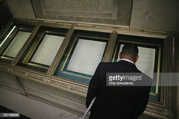One of 215 new citizens looks at the United States Constitution after a ceremony at the National Archives September 17 2012 in Washington DC The...