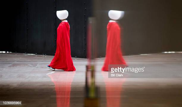 One of a dozen protesterers dressed in The Handmaid's Tale costumes walks in a circle in the atrium of the Hart Senate Office Building during the...