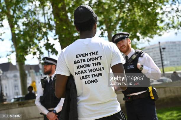 One of a small group of anti-lockdown protesters speaks to a police officer as they gather outside New Scotland Yard in Victoria, London on May 2...