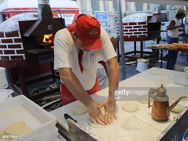 One of a team of professional neapolitan pizza makers kneads dough to give away free pizza margheritas in Dante square in downtown Naples on August...