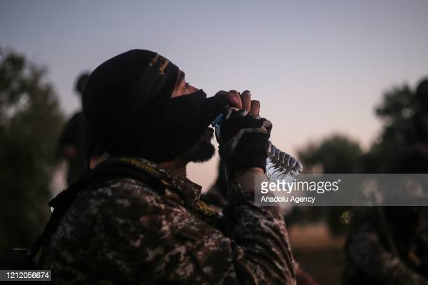 One of AlQuds Brigades the armed wing of Islamic Jihad Movement drinks water as they keep guard at the border between Gaza and Israel amid...