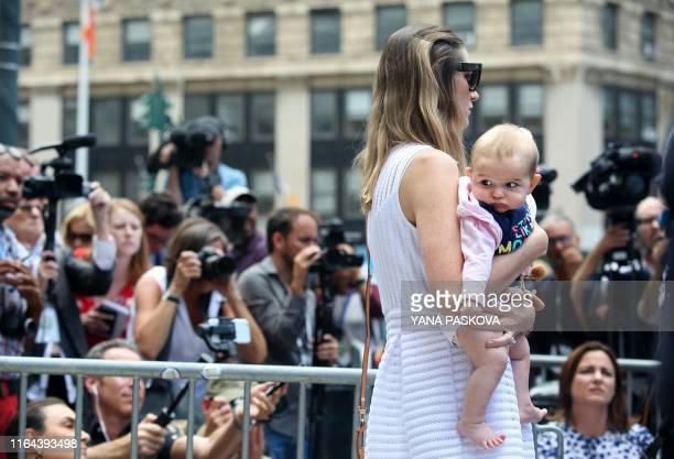One of deceased financier Jeffrey Epstein's alleged victims and her baby listen to discrimination attorney Gloria Allred talk to the press outside...